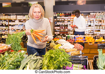 Pensive mature woman buying fresh vegetables