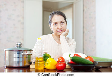 pensive mature woman with  vegetables