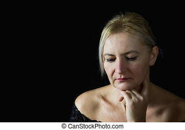 Pensive middle aged woman supporting her chin by hand