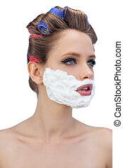 Pensive model in hair curlers with shaving foam