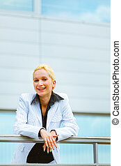 Pensive modern business woman leaning on railing at office building
