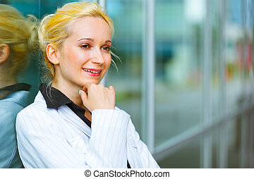 Pensive modern business woman with hand near face standing near office building
