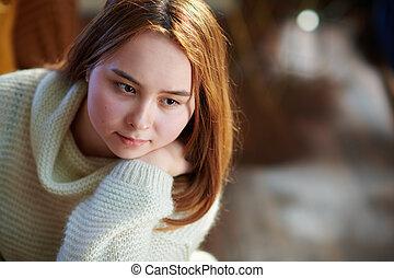 pensive modern teen girl at modern home in sunny winter day