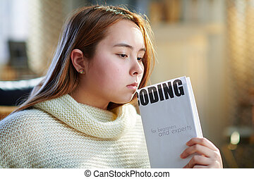 pensive modern young woman holding educational coding book