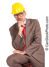 pensive old construcion engineer sitting on chair on white ...