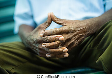 pensive old man sitting on bench in park - closeup of hands...