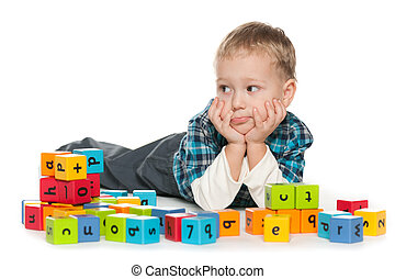 Pensive preschool boy with blocks