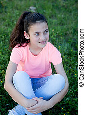 Pensive preteen girl with blue eyes sitting on the grass