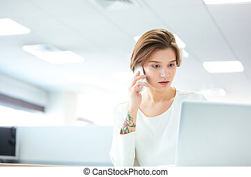 Pensive pretty young woman talking on cell phone in office