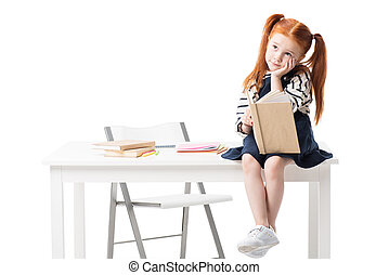 pensive red haired schoolgirl holding book while sitting on table and looking away isolated on white