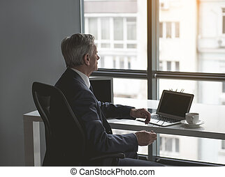 Pensive retire male in office watching at street