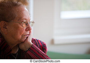 Pensive senior - An old woman sits thoughtfully at the ...