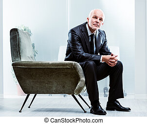 Pensive senior businessman sitting in an armchair