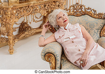 Pensive senior lady relaxing on confortable armchair - ...