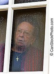 pensive senior looks sad from a window