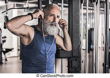 Pensive senior male is listening to music in athletic center
