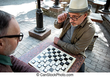 Pensive senior male pensioners playing chequers