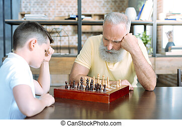 Pensive senior man and his grandson playing chess
