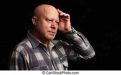 Pensive senior man. Isolated on black
