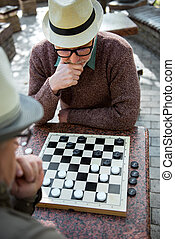 Pensive senior man playing chequers with his friend