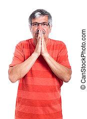 Pensive senior man praying