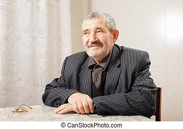 Pensive senior man sitting at table