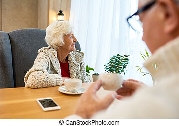 Pensive Senior Woman at Table in Cafe - Portrait of smiling...
