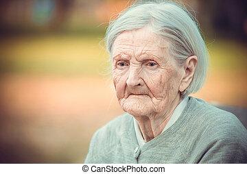 Pensive senior woman in park