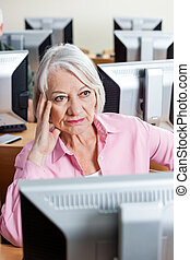 Pensive Senior Woman Sitting At Computer Desk In Classroom