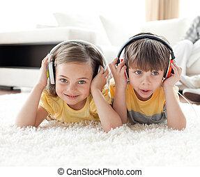 Pensive siblings listening music
