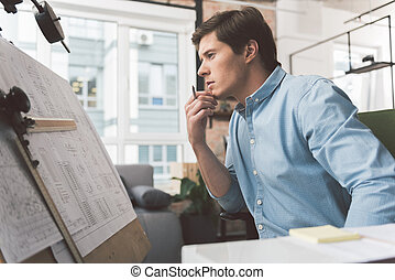 Pensive skillful man is sitting in cozy office
