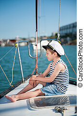 pensive small boy in captain hat sitting luxury yacht board...
