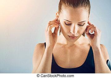 Pensive sporty brunette listening to music