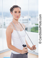 Pensive sporty woman holding skipping rope