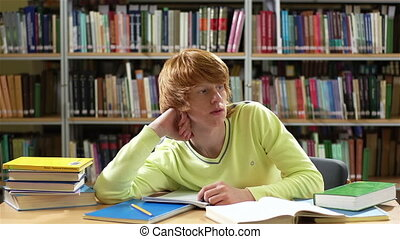 Library student thinking over some ideas then writing them down in his copybook