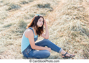 pensive teen girl in a field with str