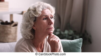 Pensive thoughtful senior grandma looking away thinking of ...
