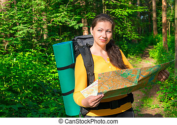 pensive tourist with map in a summer forest