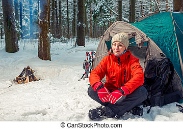 pensive tourist woman sits near a tent in a winter forest
