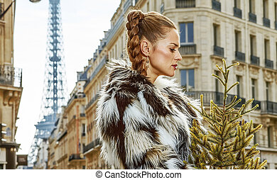 pensive trendy fashion-monger with Christmas tree in Paris -...