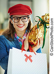pensive trendy woman in glasses with egg and shopping bag