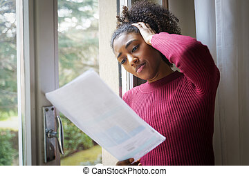 Pensive upset young African American woman reading bad notification