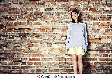 Pensive woman against a brick wall
