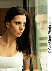 Pensive woman at home looking by the window
