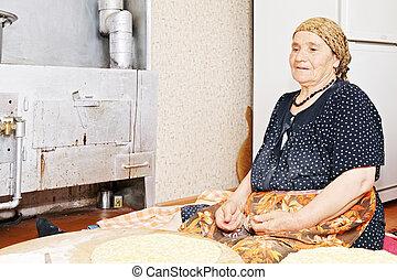 Pensive woman baking bread
