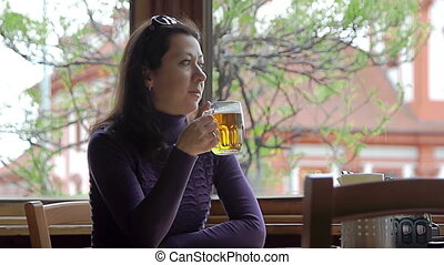 Pensive woman drinking beer while sitting in cafe