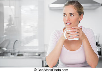 Pensive woman having coffee