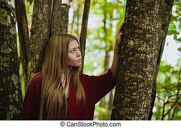 Pensive woman in a beautiful forest