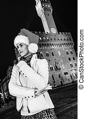 pensive woman in Christmas hat in Florence looking into...
