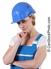 Pensive woman in overalls and a hard hat